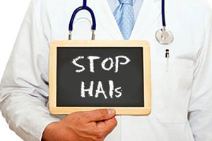 Picture of a Doctor holding a chalkboard that says Stop HAIs
